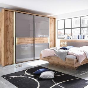Schlafzimmer in Wildeiche-Nachbildung mit abgesetzten Glasfronten in basaltgrau, Dreh-/Schwebetürenschrank und Bettanlage mit 2 Nachtschränken